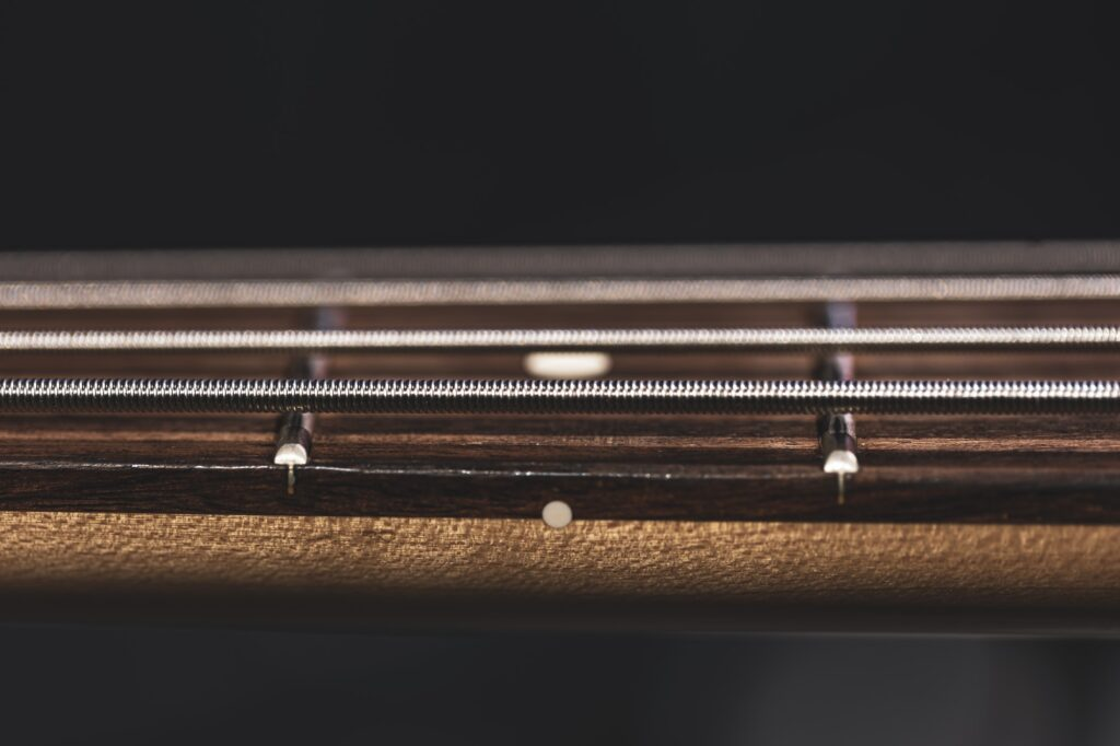 Close-up of strings on the fretboard of a bass guitar.