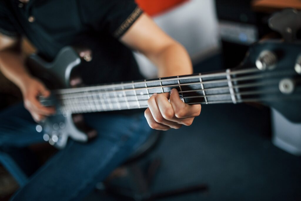 Close up view of musician plays bass guitar indoors