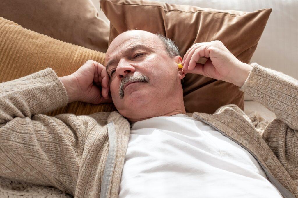 Senior stressed man holding a yellow earplug trying to sleep having insomnia