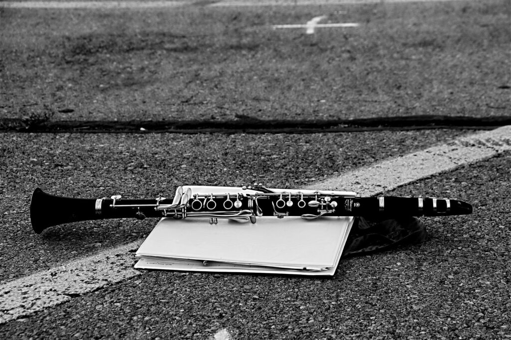 Monochromatic image of clarinet lying on a white binder in a high school parking lot.